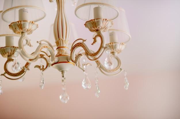 Belle lumière jaune et bleue se reflétant à travers des cristaux de verre tchèque brossés suspendus à un lustre vintage