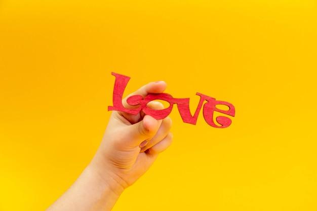 Belle main d'adolescente tenant le mot amour en bois. concept de la saint-valentin.