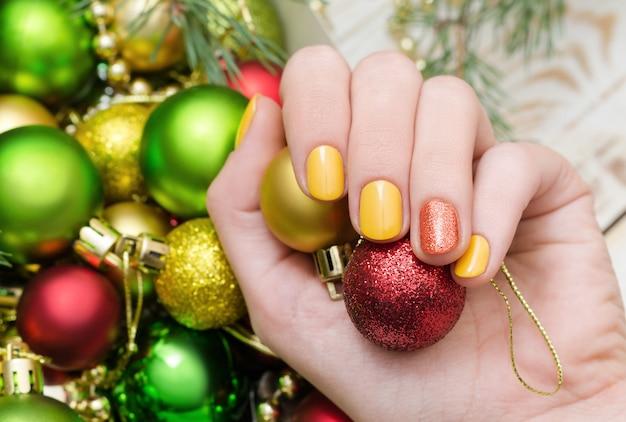Belle main féminine avec la conception des ongles jaune. manucure de noël.