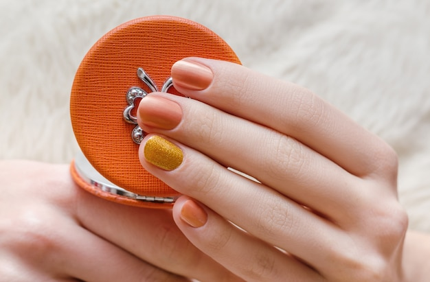 Belle main féminine avec la conception des ongles orange