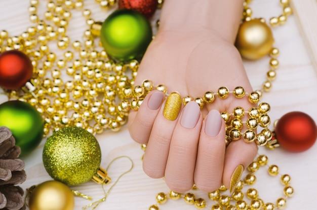 Belle main féminine avec un design ongle beige. manucure de noël.