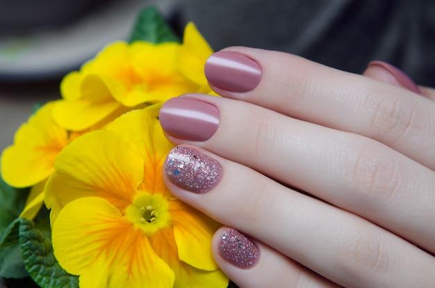 Belle main féminine avec un design ongle beige.