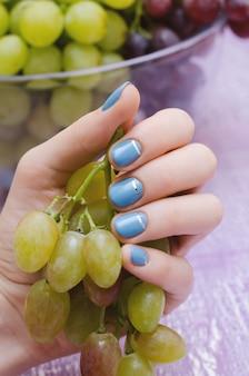 Belle main féminine avec un design ongle bleu.