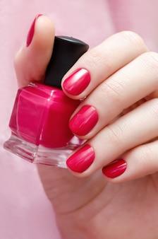 Belle main féminine avec un design ongle rose.