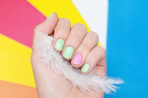 Belle main féminine avec un design ongle vert et rose clair.