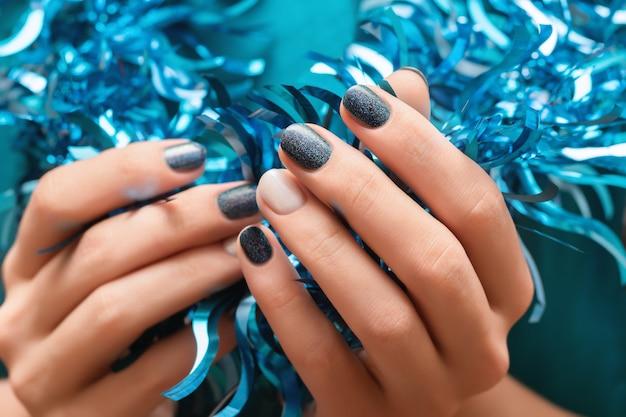 Belle main féminine avec des ongles bleus