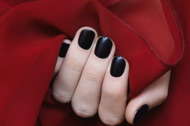 Belle main féminine avec des ongles violets