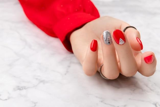 Belle main féminine soignée avec un design d'ongle de noël