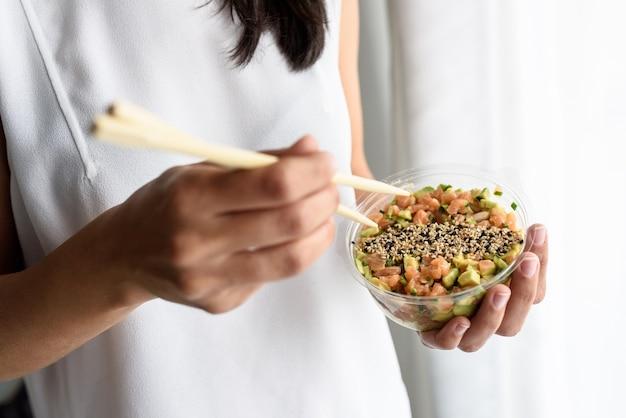 Belle main féminine tenant des baguettes pour manger un délicieux tartare de thon