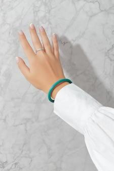 Belle main de femme avec la conception d'ongles d'été de printemps sur fond gris marbré