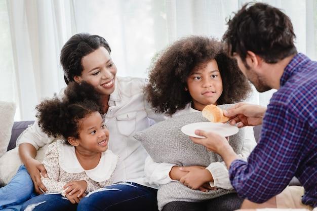 Belle maison famille heureuse vivant ensemble dans le salon père mère jouant avec sa fille mix race.