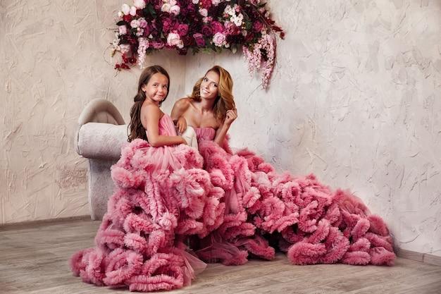 Belle maman blonde mince en robe longue et jeune fille avec des fleurs
