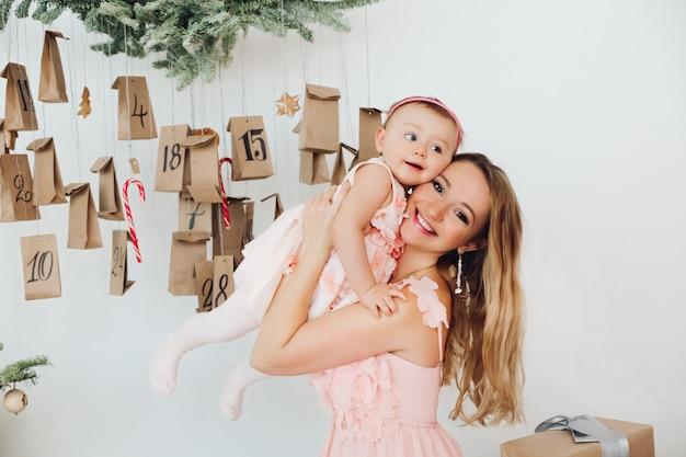 Belle maman avec une petite fille en robes roses jouant près de la décoration de noël.