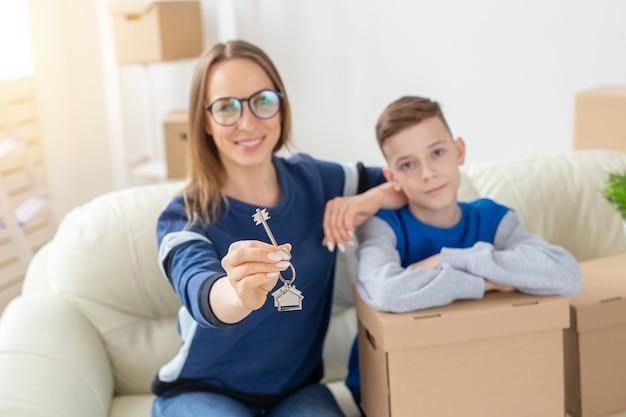 Une belle maman et son fils flous tiennent les clés d'un nouvel appartement après la pendaison de crémaillère. nouveau