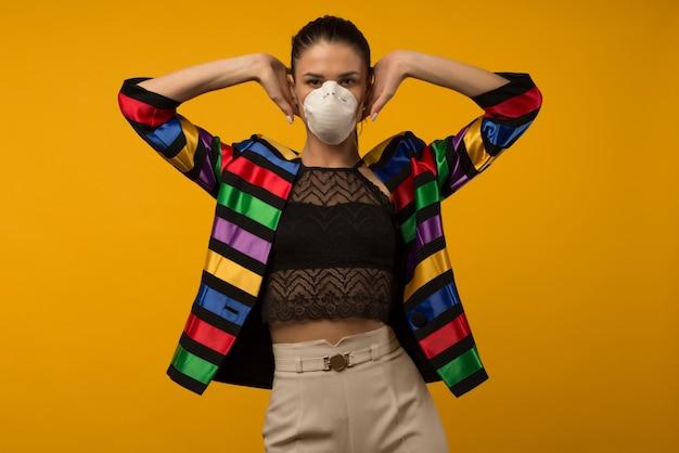 Belle mannequin fille mince posant dans un respirateur protecteur sur fond jaune. veste couleur arc-en-ciel de la communauté lgbt