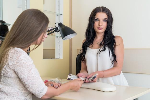 Belle manucure de femme montrant l'échantillonneur de couleur au client