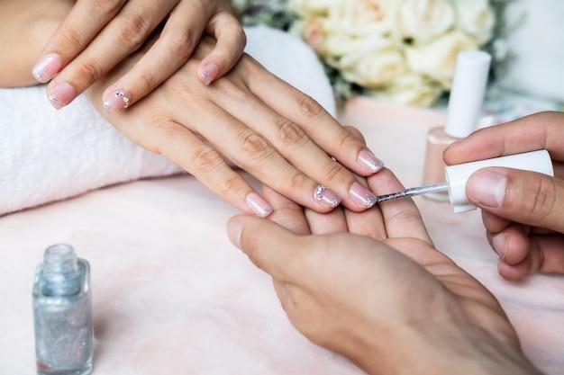 Belle manucure ongles peinture avec des paillettes et du vernis dans le salon de manucure