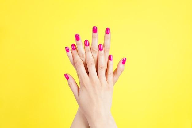 Belle manucure, vue de dessus. belles mains d'une jeune femme sur fond jaune.