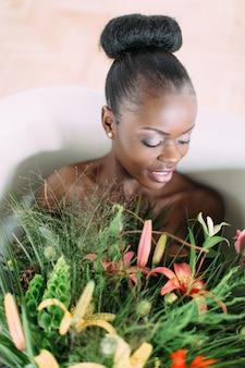 Belle mariée afro-américaine dans un bain décoré. belle femme afro-américaine dans le bain avec bouquet