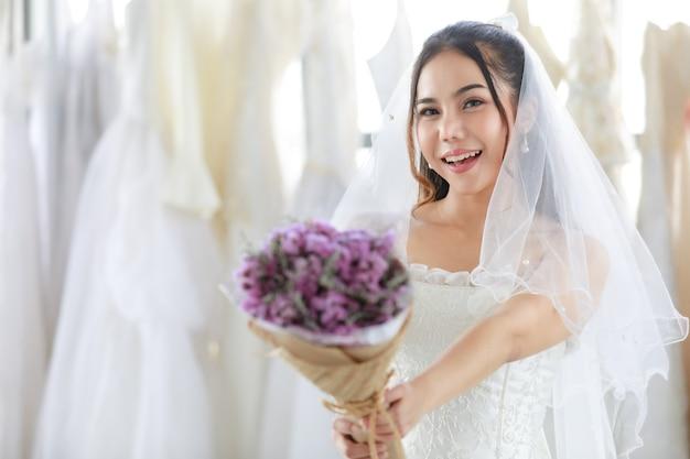 Belle mariée asiatique en robe blanche avec voile de dentelle de cheveux transparents debout souriant regardant la caméra tenant un bouquet de fleurs de mariage parfumées pourpres dans les mains au premier plan flou dans le dressing.
