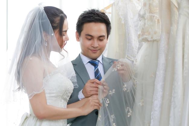 Belle mariée asiatique en robe de mariée blanche avec un voile de dentelle de cheveux transparent debout souriant tenant un regard sur d'autres vêtements avec un jeune beau marié en costume formel gris dans le dressing.