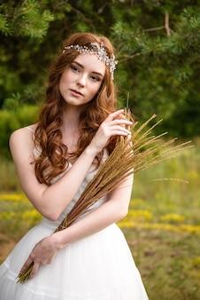 Belle mariée aux cheveux roux tenant des épis de blé dans ses mains
