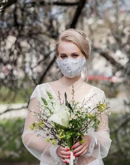 Belle mariée blonde dans une robe de mariée et un masque de protection médicale sur son visage,
