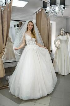 Belle mariée blonde posant en robe de mariée