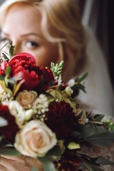 Belle mariée blonde regarde par-dessus le bouquet de mariage rouge foncé