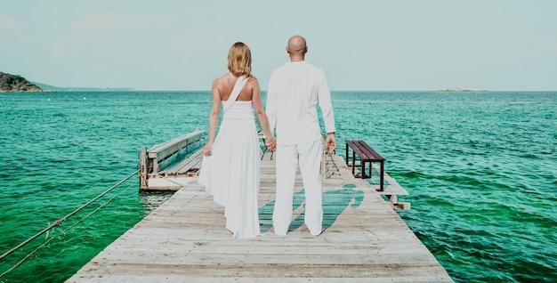 Belle mariée blonde en robe de mariée blanche se tient au bord de la mer. mer tropicale et rochers en arrière-plan. concept de vacances d'été.