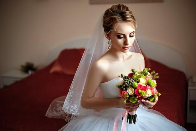 Belle mariée avec bouquet assis sur un lit.