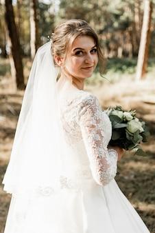 Belle mariée avec un bouquet dans ses mains à l'extérieur. mariée aux cheveux blancs dans la forêt. portrait de la mariée. robe de mariée élégante. fille un jour de mariage.