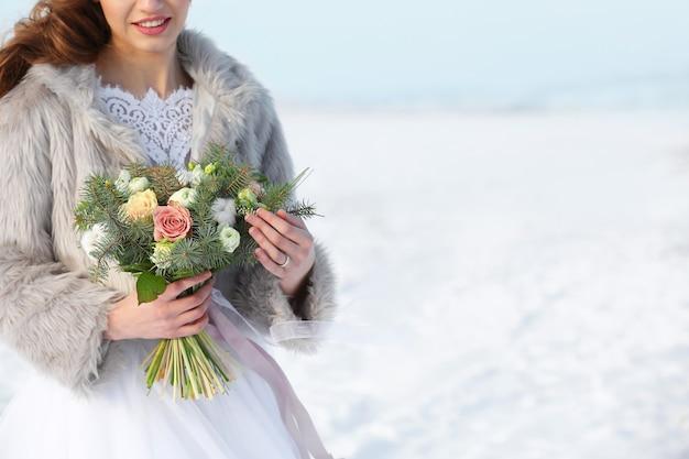 Belle mariée avec bouquet à l'extérieur le jour de l'hiver