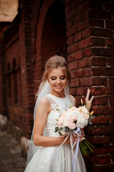 Belle mariée avec bouquet de fleurs de mariage, jolie femme en robe de mariée. heureuse jeune mariée. mariée avec maquillage et coiffure de mariage. mariée souriante. jour de mariage. superbe mariée. mariage.