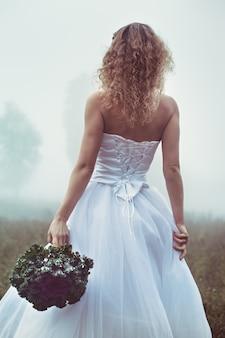 Belle mariée avec un bouquet sur fond de champ brumeux