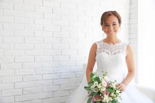 Belle mariée avec bouquet de mariage sur mur de briques blanches