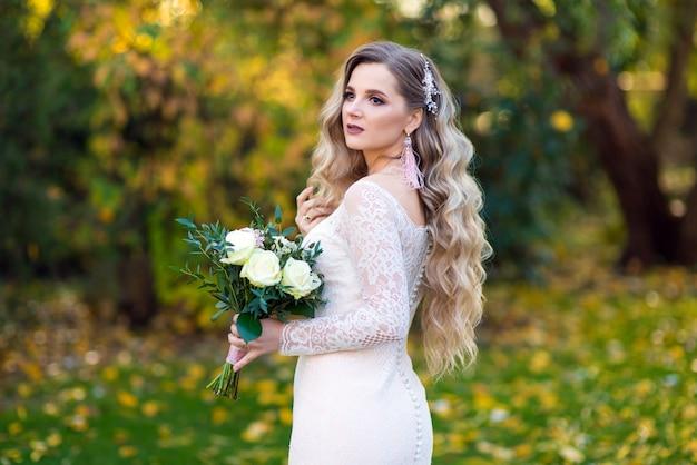 Belle mariée avec un bouquet de mariée dans le jardin dans le jardin
