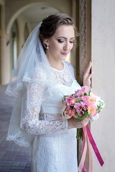 Une belle mariée avec un bouquet de mariée en mains