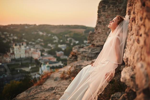 Belle mariée brune dans une robe de mariée et un long voile posant près des montagnes à l'extérieur de la ville