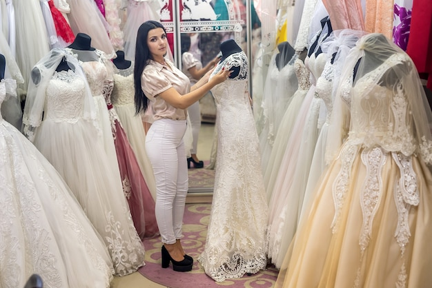 Belle mariée en choisissant la robe de mariée dans le salon