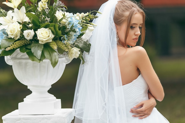 Belle mariée dans une magnifique robe de mariée posant au milieu de la verdure dans la rue. concept de mariée pour les robes publicitaires