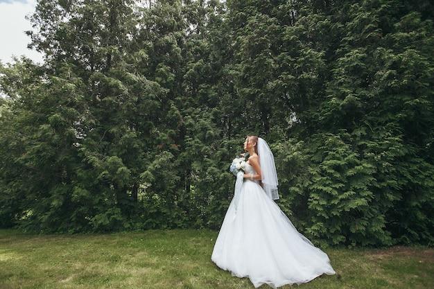 Belle mariée dans une magnifique robe de mariée posant au milieu de la verdure dans la rue. fille pose dans une robe de mariée pour la publicité. concept de mariée pour les robes publicitaires.