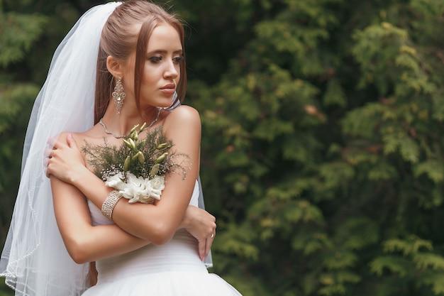 Belle mariée dans une magnifique robe de mariée posant parmi la verdure dans la rue. concept de mariée pour les robes publicitaires