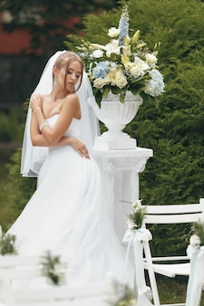 Belle mariée dans une magnifique robe de mariée posant parmi la verdure dans la rue.