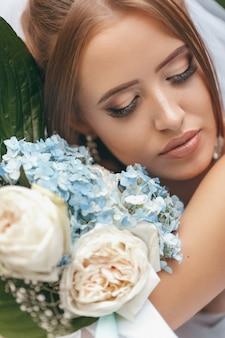Belle mariée dans une magnifique robe de mariée posant parmi la verdure dans la rue