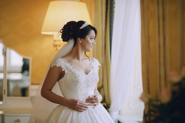 Belle mariée dans une robe blanche et une couronne sur sa tête debout près de la fenêtre
