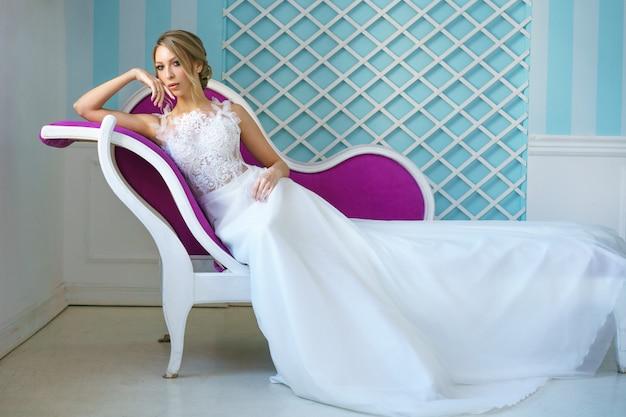 Belle mariée dans une robe blanche est allongée sur le canapé