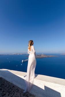 Belle mariée dans une robe blanche posant dans le contexte de la mer méditerranée à thira, santorin.