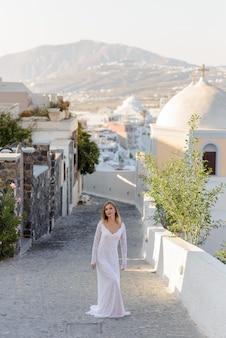 Belle mariée dans une robe blanche posant dans le contexte de la ville de thira, santorin.