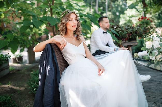 Une belle mariée dans une robe de mariée blanche et une couronne est assis sur une chaise à côté du marié